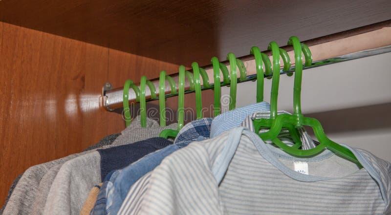 Одевать шкаф с комплементарными одеждами аранжировал на вешалках Красочный шкаф newborn, дети, младенцы вполне всех одежд, ботинк стоковое изображение
