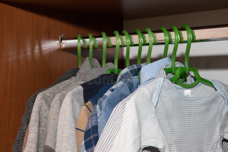 Одевать шкаф с комплементарными одеждами аранжировал на вешалках Красочный шкаф newborn, дети, младенцы вполне всех одежд, ботинк стоковое изображение rf