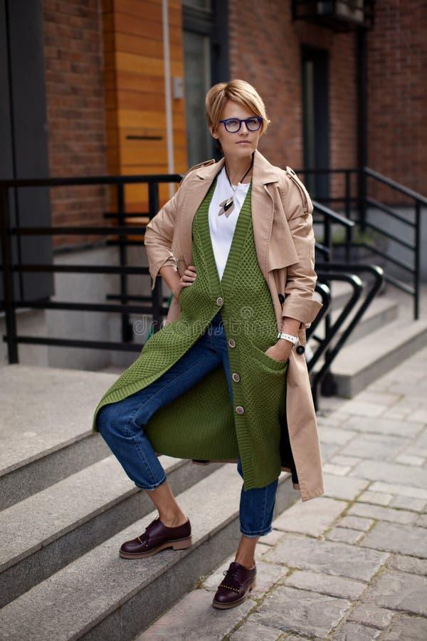 Одежда высокой моды Красивая женщина нося модные весну или падение одевает бежевое пальто канавы, длинный зеленый свитер, стоковое фото