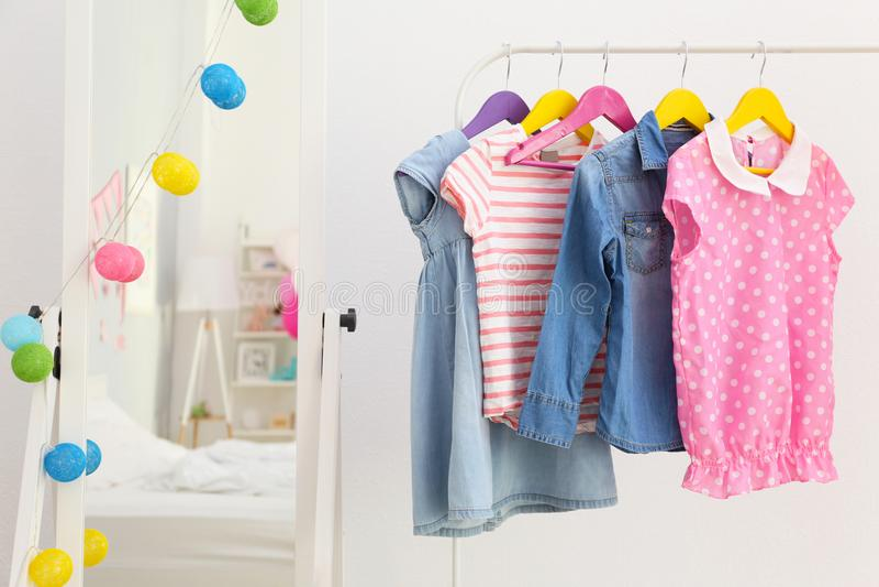 Одежда детей на стойке вешалки в одевать стоковое изображение rf