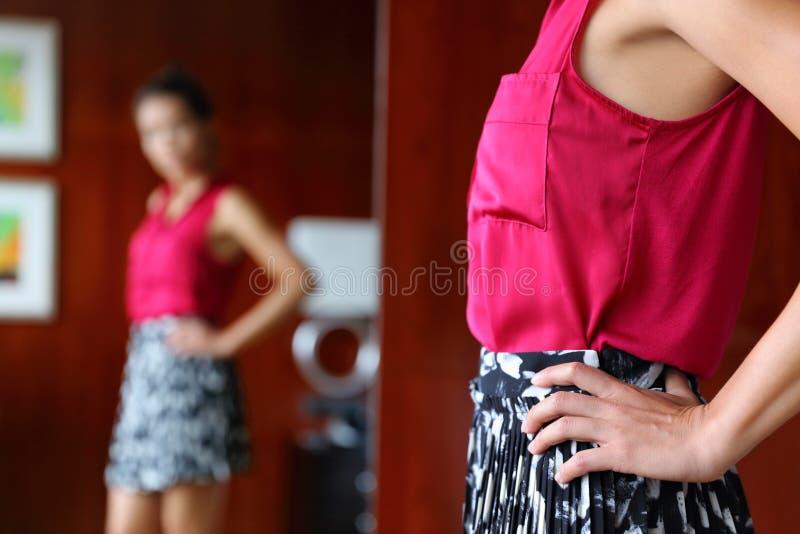 Одежда женщины пробуя смотря зеркало стоковые изображения