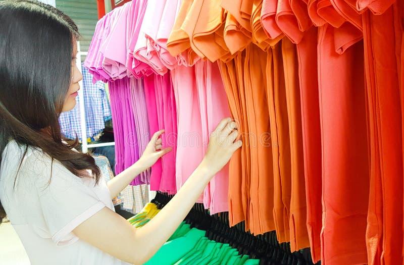 Одежда, мода, стиль и концепция людей Одежды молодой азиатской женщины покупая в магазине торгового центра Женский выбор или стоковые изображения rf