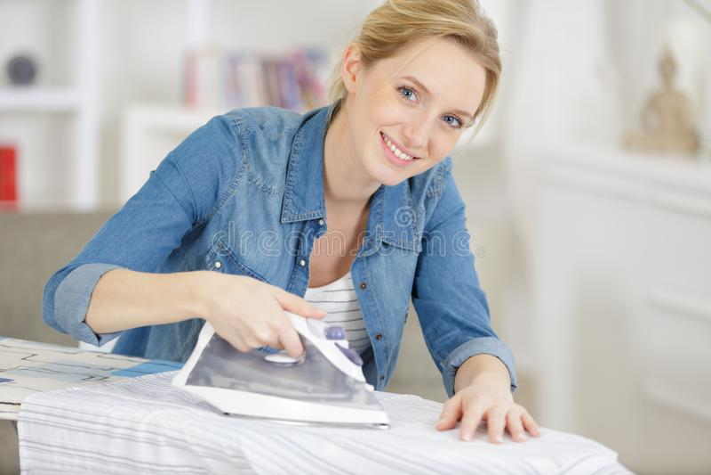 Одежда молодой женщины утюжа дома стоковые изображения