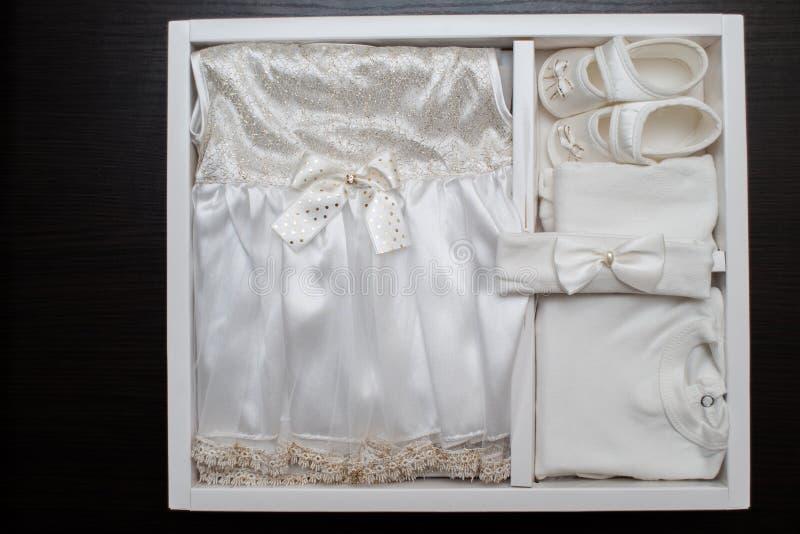 Одежда ` s детей, платье, ботинки, на темной предпосылке стоковое изображение