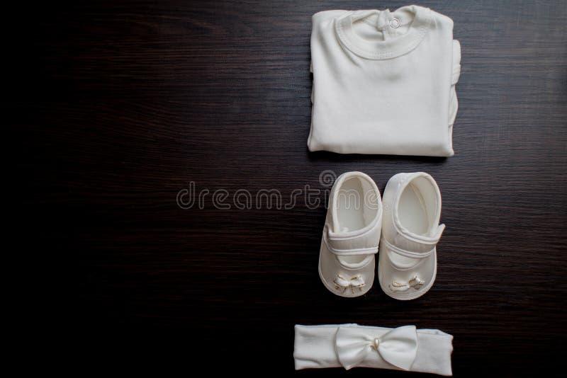 Одежда ` s детей, платье, ботинки, на темной предпосылке стоковое фото