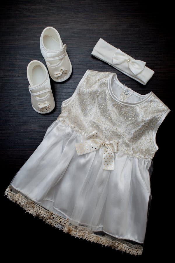 Одежда ` s детей, платье, ботинки, на темной предпосылке стоковая фотография