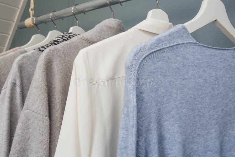 Одежды висят на шкаф одежды, белые серое и голубой, стоковые фото