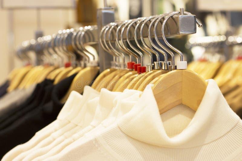 Одежды вися на вешалках в магазине, выборе концепции одежды стоковое фото