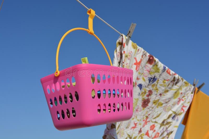Одежды и зажимки для белья в розовой корзине вися от веревки для белья стоковое изображение