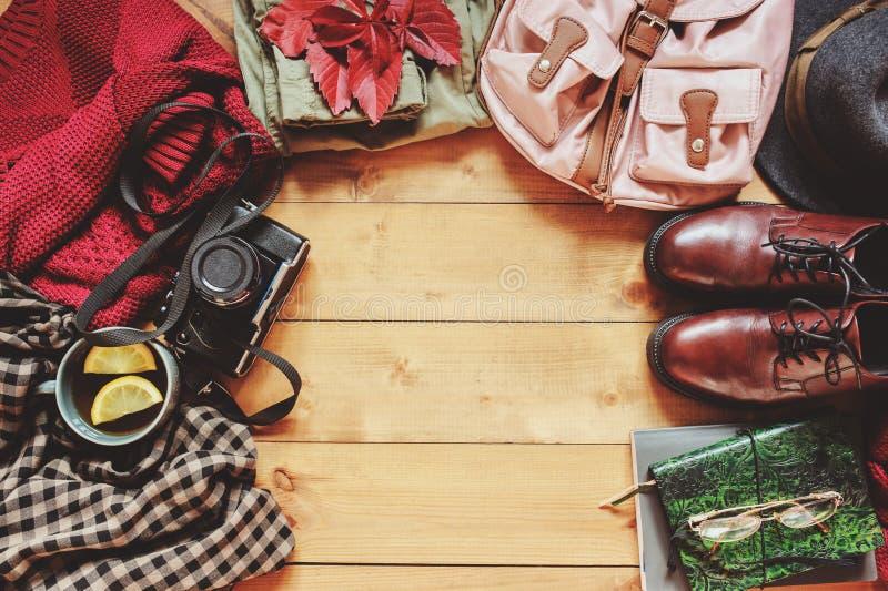 Одежды моды женщин осени установили с уютным свитером, ботинками, рубашкой шотландки, винтажной камерой фото, рюкзаком и чашкой ч стоковые изображения