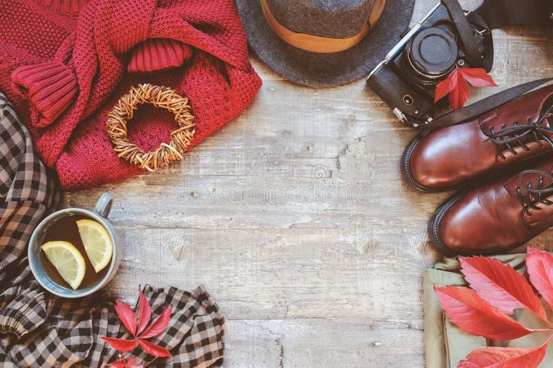 одежды моды женщин осени установили с уютным свитером, ботинками, рубашкой шотландки, винтажной камерой фото, шляпой и чашкой чаю стоковые изображения rf
