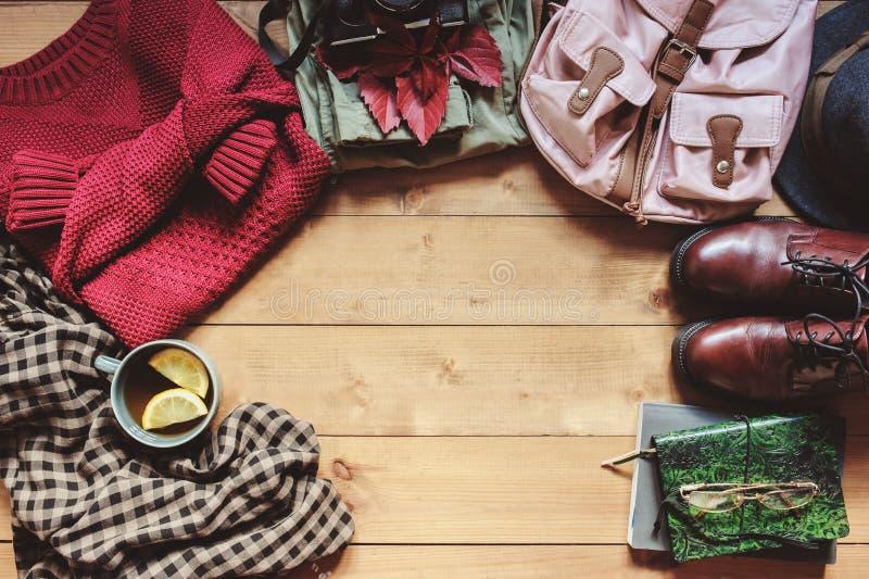 одежды моды женщин осени установили с уютным свитером, ботинками, рубашкой, винтажной камерой фото, рюкзаком и чашкой чаю стоковое фото