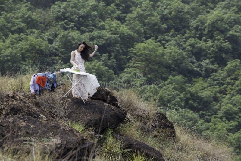 Одежды молодой женщины утюжа на утюжа доске на каменном холме save стоковая фотография rf