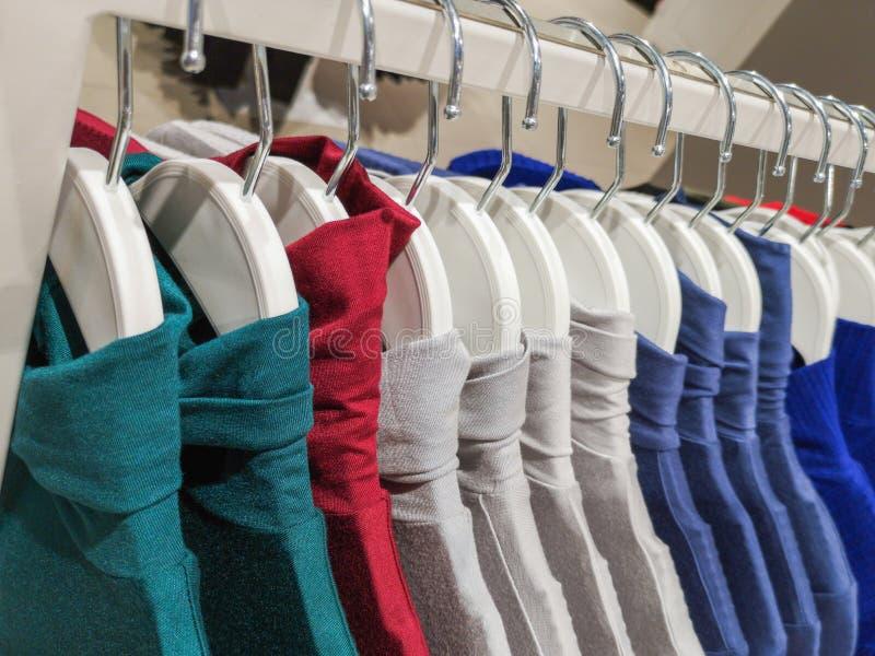 Одежды на вешалках в магазине Одежды висят на полке в магазине дизайнерской одежды в других цветах стоковое изображение rf