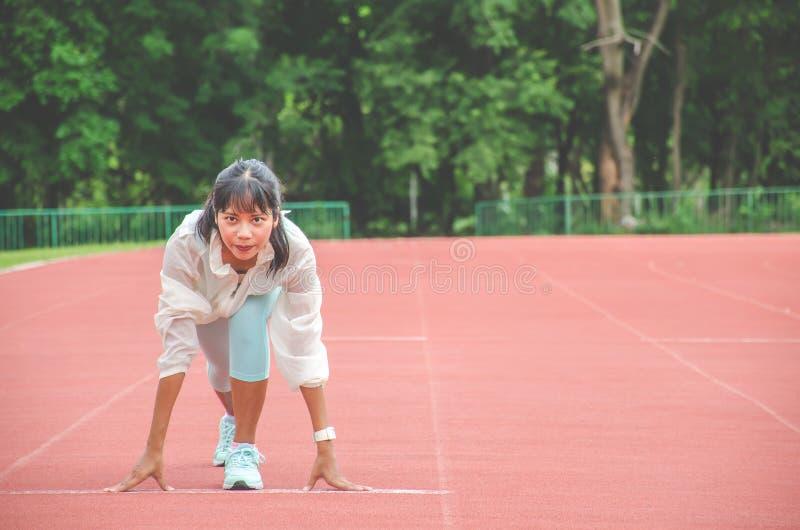 Одежды спорт молодой женщины нося и готовый для начала побежать на следе в стадионе, женщинах спорта стоковые изображения rf