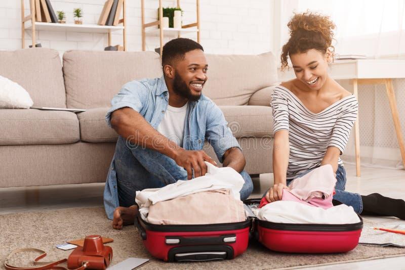 Одежды упаковки пар Афро в чемодан, подготавливая для медового месяца стоковая фотография