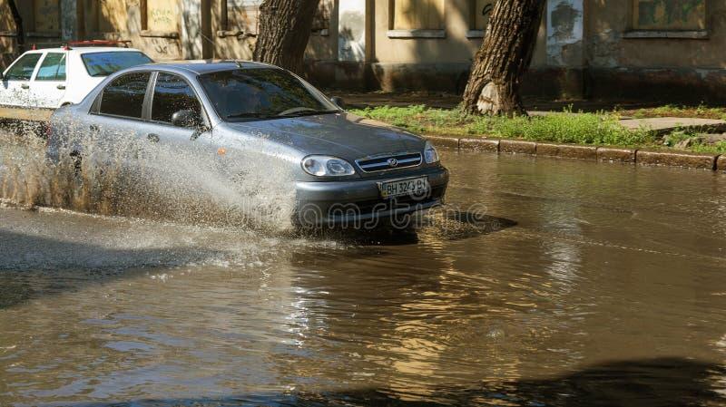 Одесса, Украина -3 июль 2018: Управлять автомобилями на затопленной дороге во время потоков причиненных дождем бушует Поплавок ав стоковое изображение