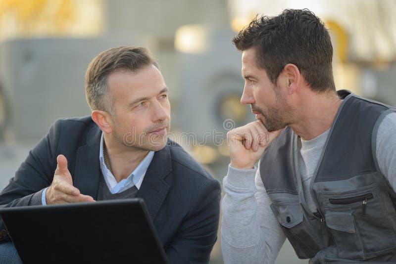Одетый человек и рабочий класс смотря ноутбук outdoors стоковая фотография rf