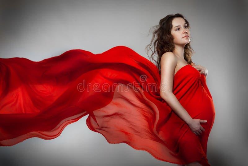 одетьйте супоросую красную женщину стоковые фото