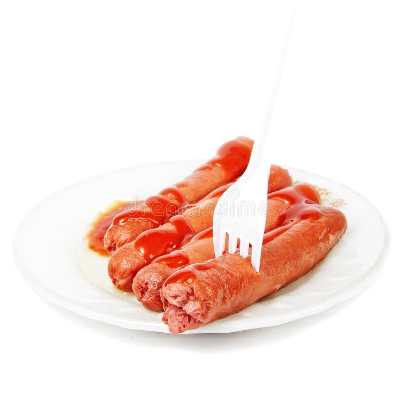одетьнные сосиски ketchup вилки стоковое фото