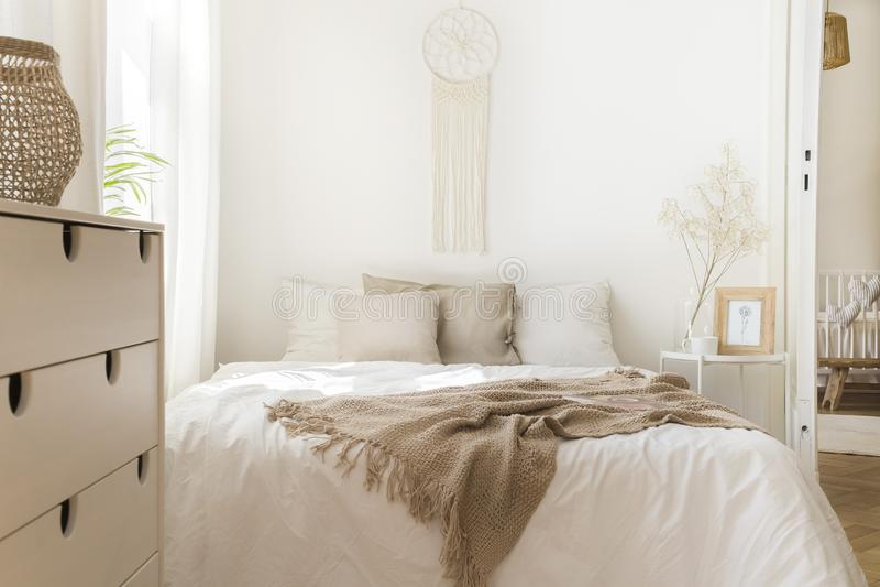 Одеяло на белой кровати с подушками и деревянным шкафом в минимальном естественном интерьере спальни стоковые фотографии rf