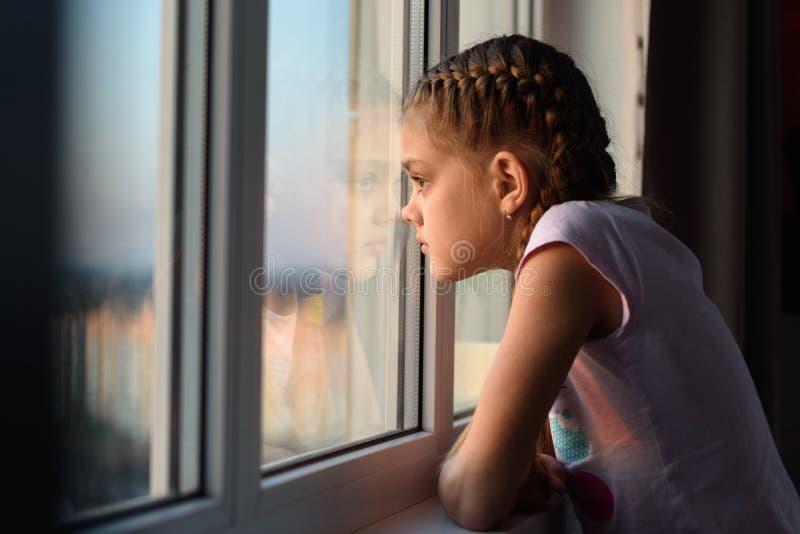 Одиннадцатилетняя девочка, изолированная от скуки, смотрит в окно стоковая фотография