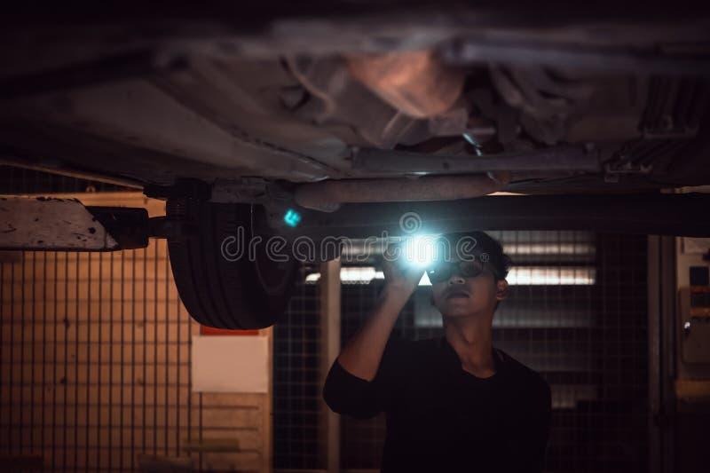 Одиноко азиатские мужчины светят фонари для осмотра автомобиля под шасси автомобиля в старом заброшенном гараже на ночном месте стоковые фотографии rf