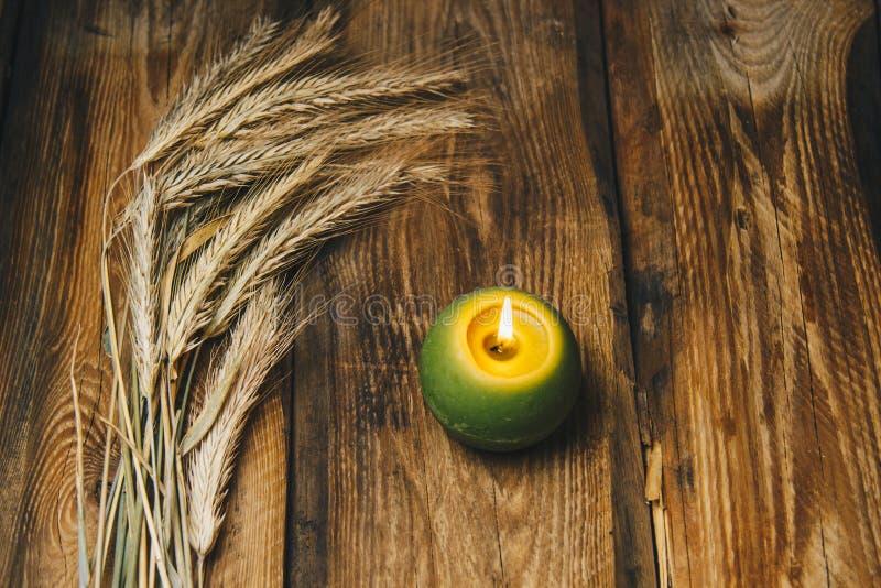 Одиночная зеленая шарообразная свеча с колоском пшеницы горит на деревенском конце-вверх деревянного стола r стоковое фото