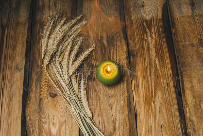 Одиночная зеленая шарообразная свеча с колоском пшеницы горит на деревенском конце-вверх деревянного стола r стоковые фотографии rf