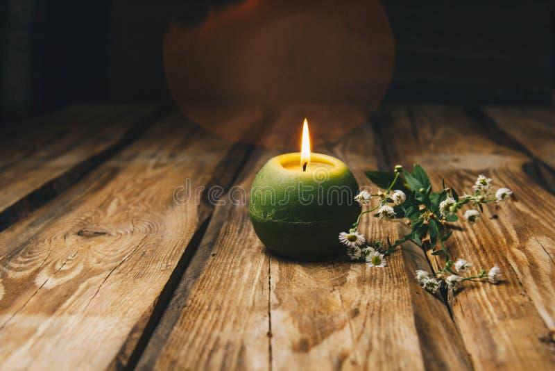 Одиночная зеленая шарообразная свеча с сухим цветком горя на деревенс стоковые изображения