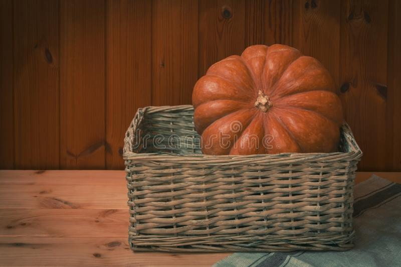 Одиночная тыква в плетеной корзине на деревянном столе стоковые изображения rf