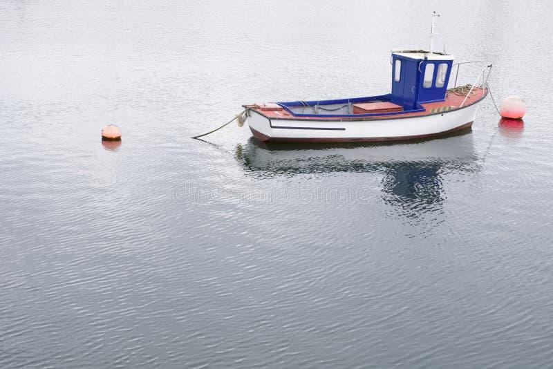 Одиночная шлюпка красная и голубая деревенская деревянная на море причаленная Марина стоковое изображение rf