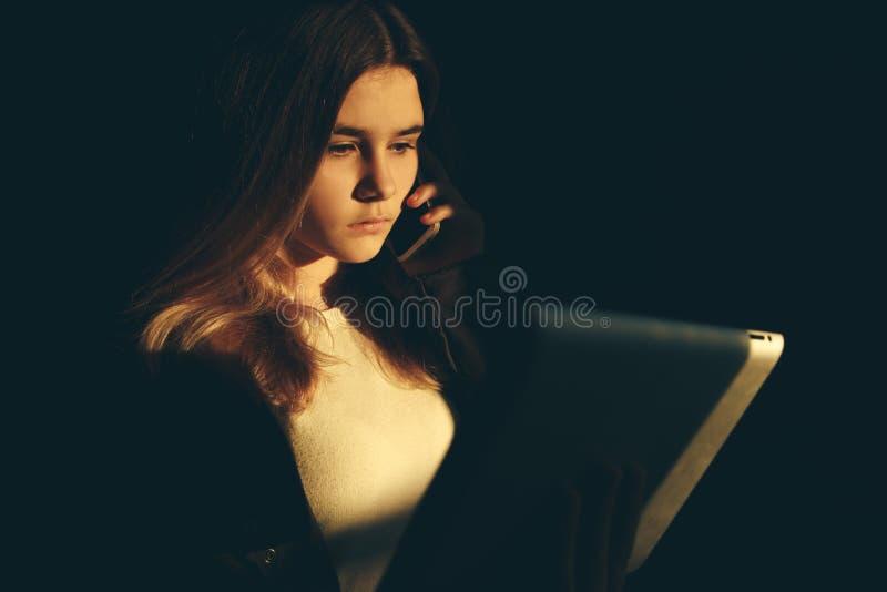 Одиночное унылое предназначенное для подростков удерживание мобильный телефон сетуя сидеть на кровати в ее спальне с темным свето стоковое фото