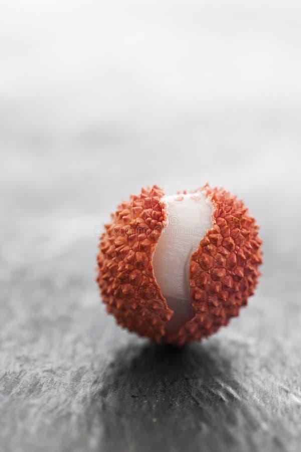Одиночное lychee на шифере против света стоковое фото