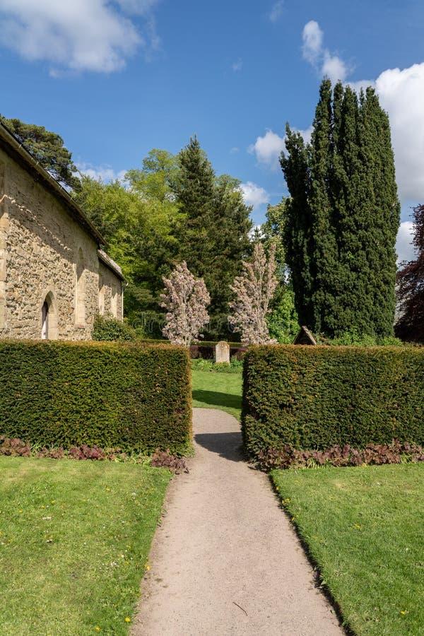 Одиночный могильный камень между 2 цветя деревьями в кладбище стоковые фотографии rf
