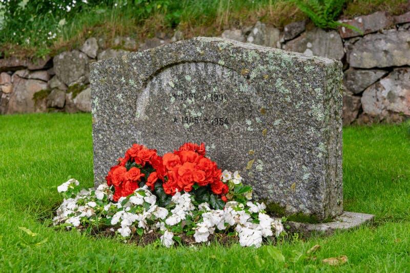 Одиночный могильный камень с красными и белыми цветками стоковые изображения rf