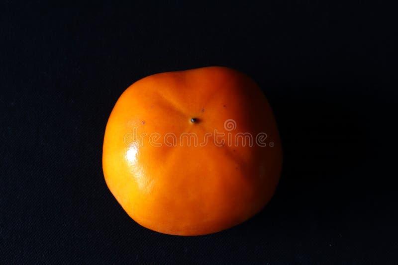 Одиночный оранжевый плод хурмы против черной предпосылки стоковая фотография rf