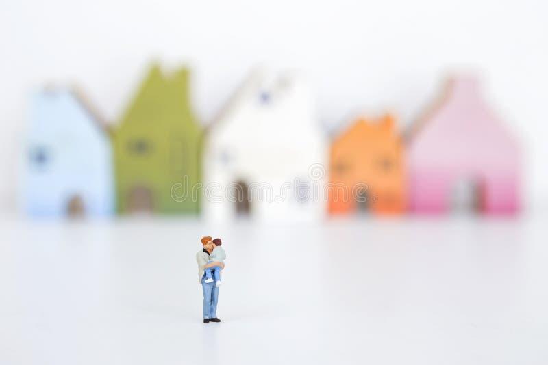 Одиночный папа, человек держа мальчика над запачканным красочным миниатюрным домом стоковое изображение