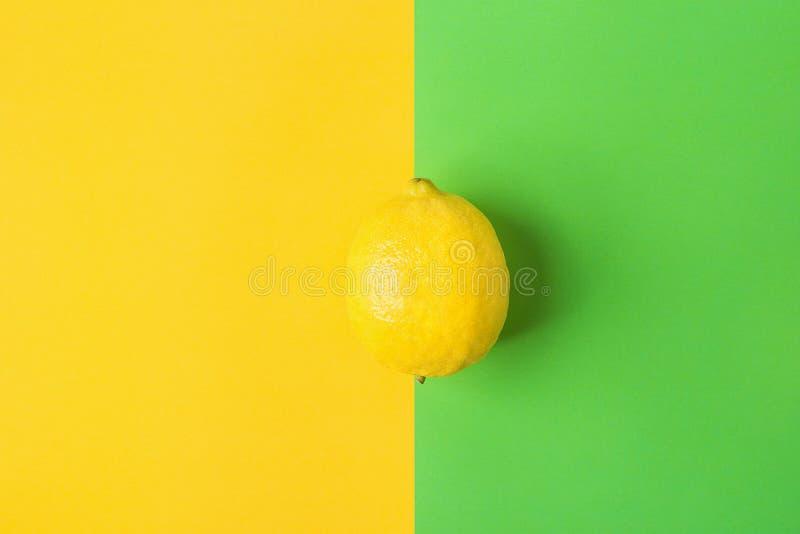 Одиночный яркий зрелый лимон на предпосылке контраста от цветов сочетания из желтых зеленых Введенное в моду творческое изображен стоковые фото