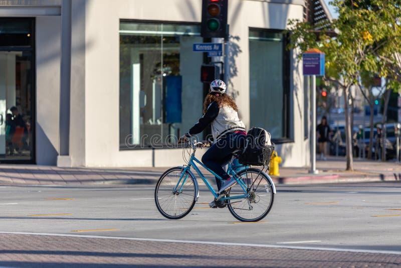 Один велосипед катания молодой женщины через пересечение стоковые изображения