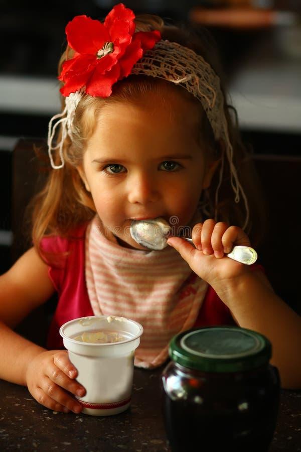 Один годовалый ребёнок в красном держателе цветка есть югурт сама для завтрака дома стоковые фотографии rf