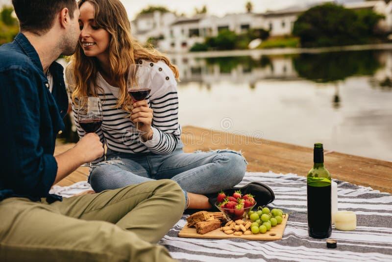 Один другого пар целуя на дате сидя около озера Соедините в любов сидя на деревянном доке около вина озера выпивая и стоковые изображения rf