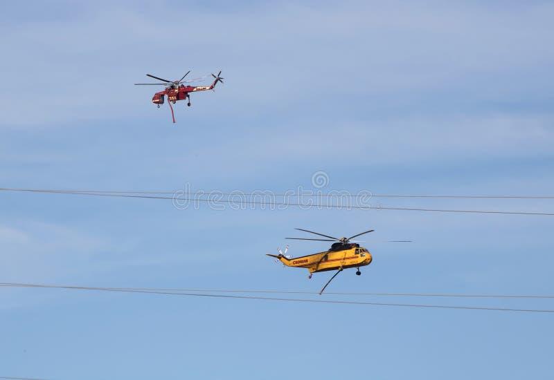 Один другого пропуска вертолетов огня красного цвета и желтого цвета в перестрелке стоковое фото rf