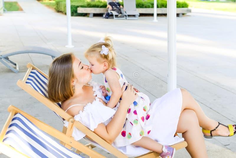 Один другого счастливой матери и дочери целуя во время ослаблять в deckchair в рекреационной зоне парка города Воссоздание семьи, стоковые изображения