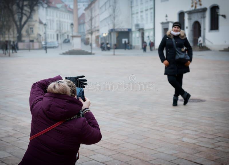 Один друг принимает другое фото Подруги сфотографированы около привлекательностей стоковые изображения