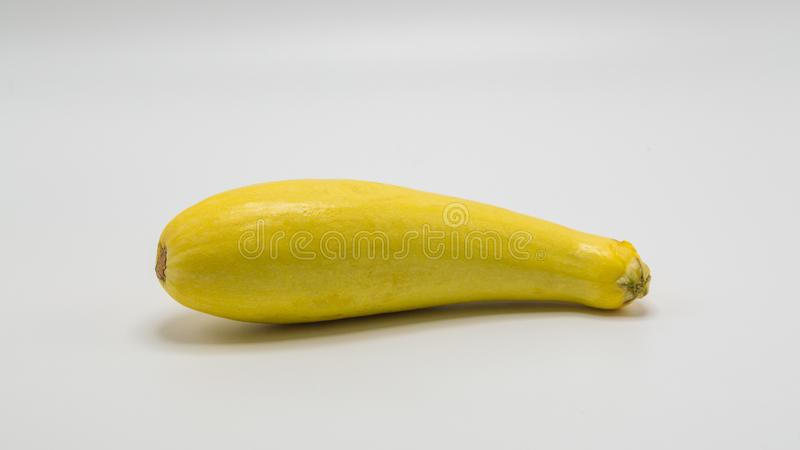 Один желтый сквош лета на белизне стоковая фотография