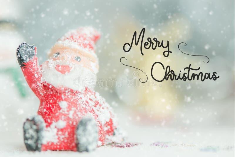 Один керамический текст Санта Клауса с Рождеством Христовым на предпосылке снежностей стоковая фотография rf