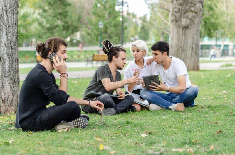 Один молодой человек говорит на мобильном телефоне Группа в составе истово работать на заднем плане с ноутбуком стоковое изображение rf