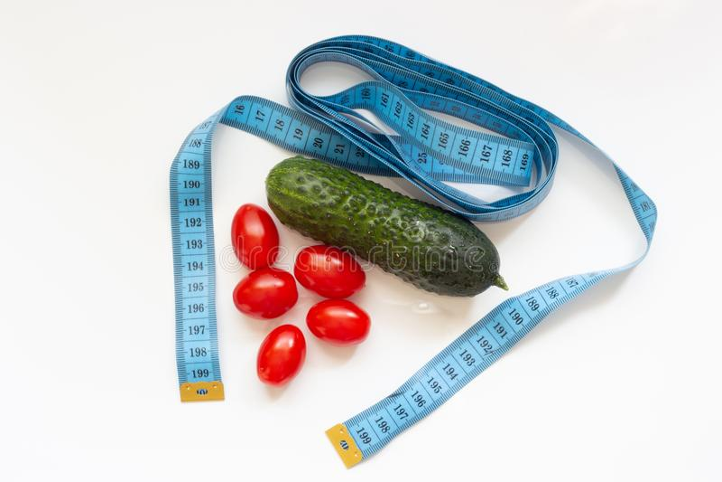 Один огурец и несколько томатов с измеряя лентой на белой предпосылке стоковое фото rf