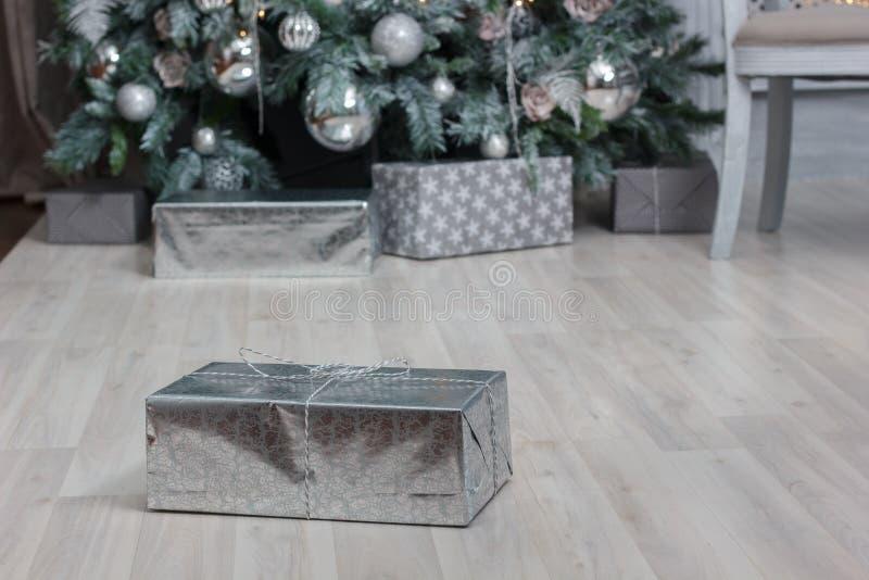 Один подарок в серебряной бумаге на поле с рождественской елкой на предпосылке стоковое фото rf